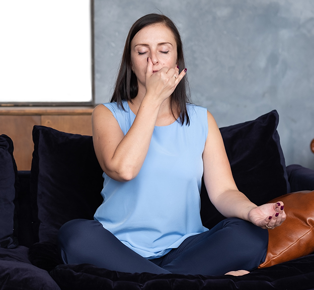 a brunette woman sitting and meditating with thumb on nose
